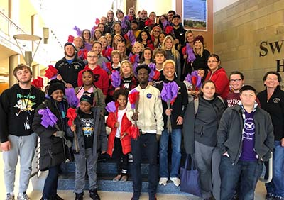 Students and family/friend members planted the over 6,000 red and purple flags