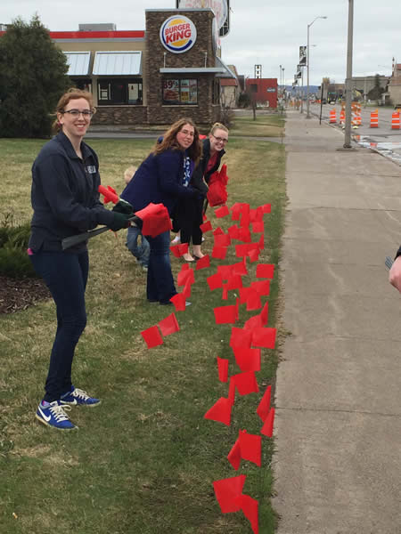 Katrina Phelps, Cassandra Grape and Melody Maleski of LSTU 115 plant flags at the corner of Belknap and Catlin to help raise awareness of sexual assault.