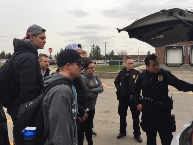 Officer Vang explains the Lino Lakes fully equipped vehicle and gear as Officer McIntosh and students in CJUS 492 listen.