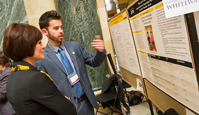 "Nick Muska presents his ""Law's Double Bar"" research to UW-Superior Chancellor Dr. Renee Wachter during Research in the Rotunda session."