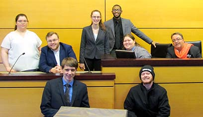 UW-Superior mock trial team 2018-2019 including (front row) Alex DeBlaey and Jeb Leone;  (second row) Arabella Gigliotti, Kenneth Benz, Autumn Bass, Julian Williams, Desiray Matthews, Scott Holmes. Not pictured, coach Cassy Burr.